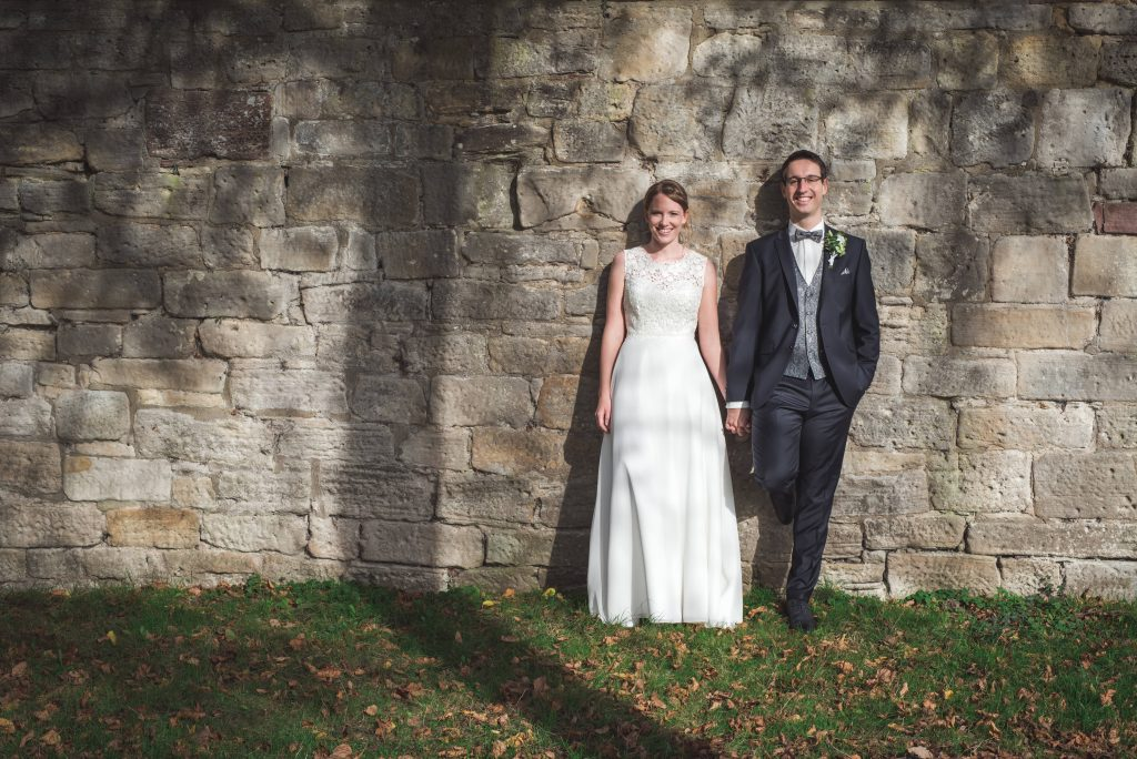 Foto eines Brautpaars vor einer Wand im Orangerie-Schlosspark Kassel