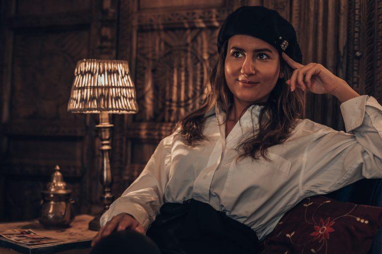 Frau mit Hut vor Tischlampe