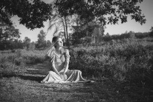 schwarz-weiß Foto einer sitzenden Frau in der Heide
