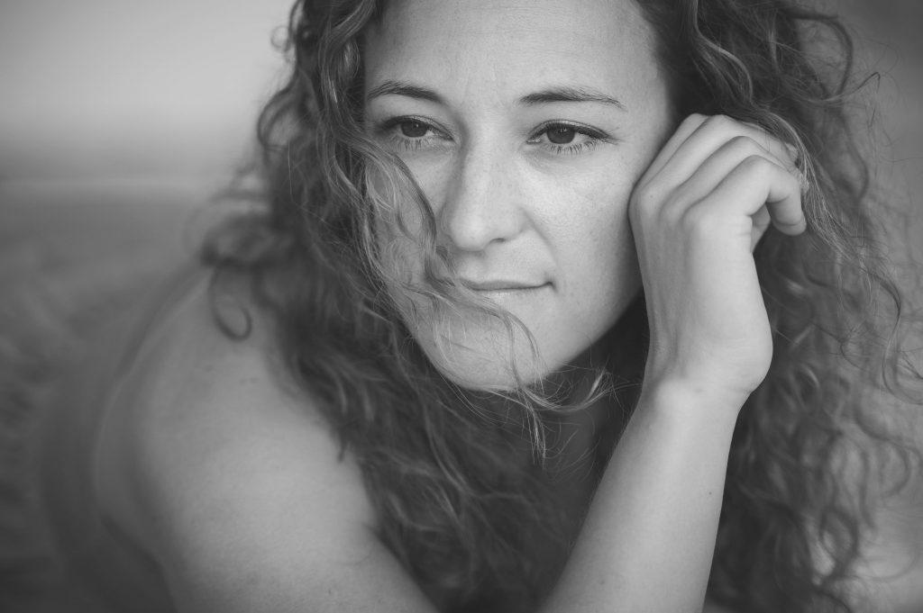 schwarz-weiß Portrait einer Frau mit Haaren im Gesicht