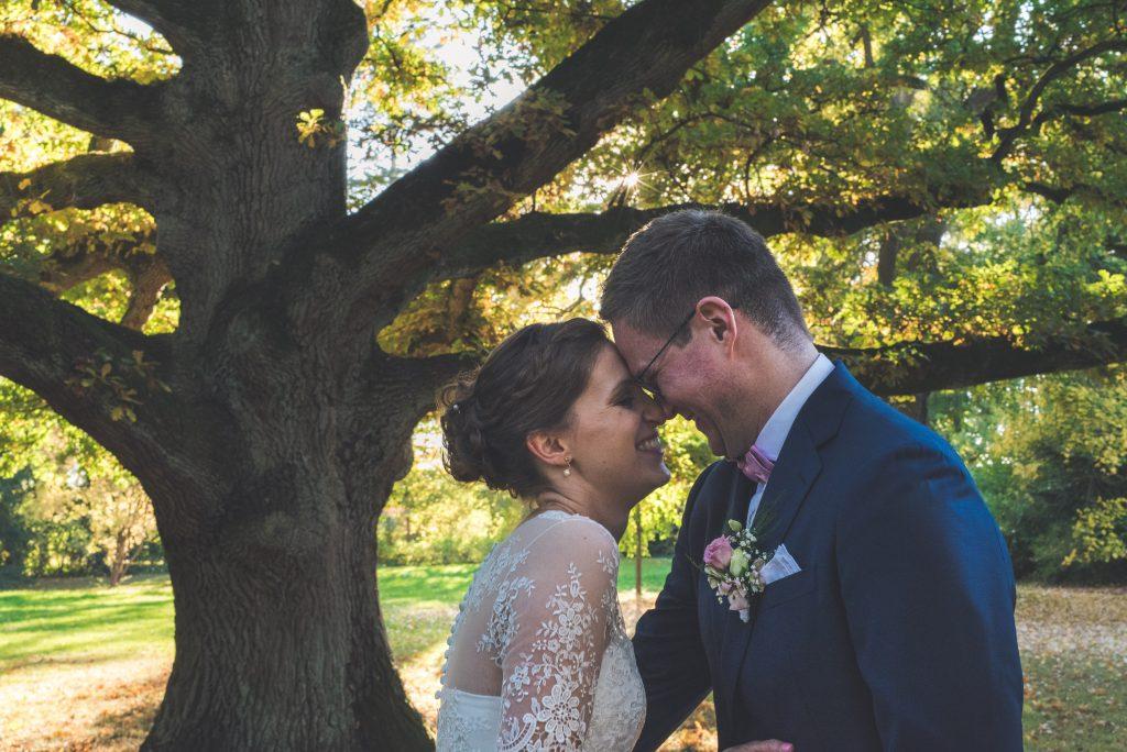 Hochzeitspaar vor einem Baum im Schlosspark Tremsbüttel